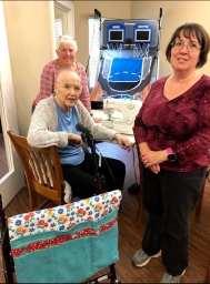 Resident and helpers with walker bag