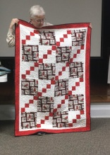 red and white quilt with birds